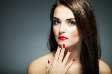 Natural woman face with red nails and lips