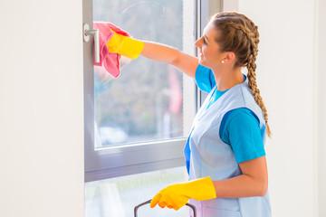 Putzfrau putzt Fenster
