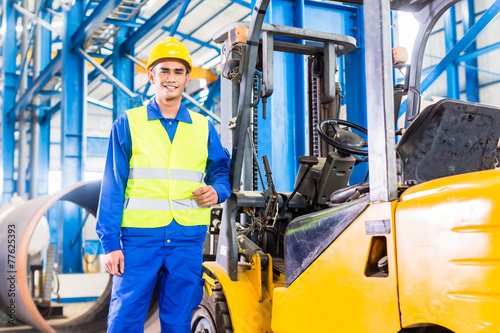 Forklift driver standing in manufacturing plant - 77625393