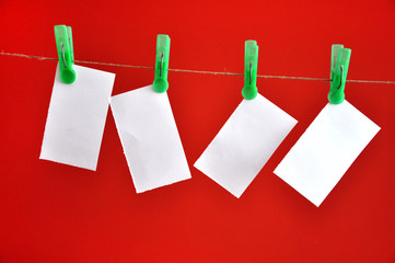Blank notes hanging clipped on the rope in front of red backgrou