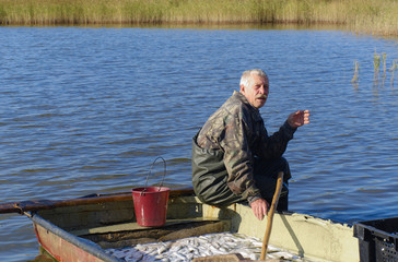 old fisherman with catch of fish