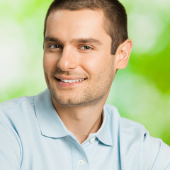 Portrait of young happy smiling attractive man, outdoors