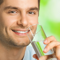 Cheerful man drinking water, outdoor