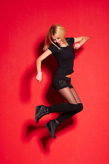 blonde lady in black posing on red