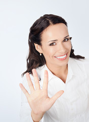 Businesswoman showing five fingers, on grey