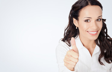 Businesswoman with thumbs up, on grey