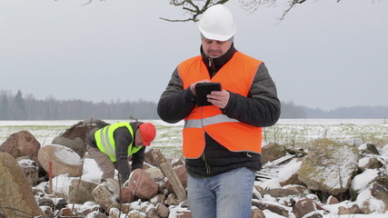 Workers near the piles of stones