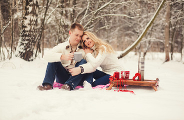 sweet couple drinking tea in the winter forest