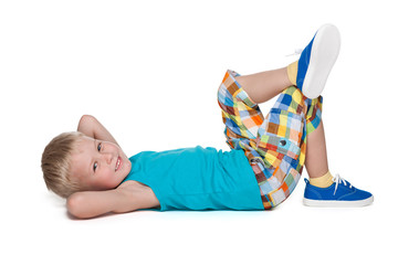 Smiling blond boy rests on the floor