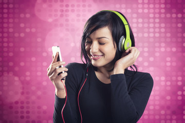 Friendly smiling girl listening to music with earphones.