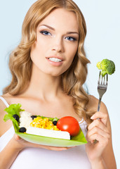 Woman with vegetarian salad, over blue