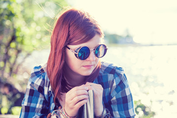 Pensive beautiful young woman in sunglasses with book near river