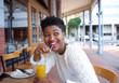 Happy african american woman drinking orange juice - 77634100