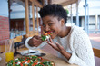 Young black woman eating vegetarian pizza
