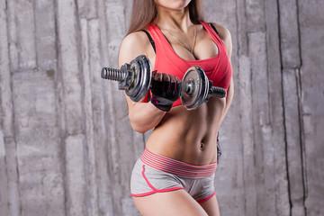 Bodybuilder girl with dumbbell