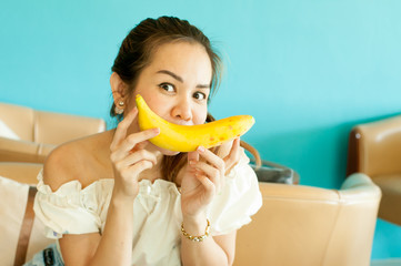 A young woman holds up a banana to her mouth, imitating a smile.
