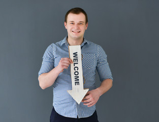 Young man holding welcome board banner