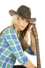 cowgirl with guitar in blue shirt hold neck