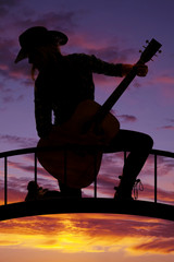 silhouette cowgirl kneel with guitar look back