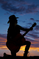 silhouette cowgirl kneel with guitar look side