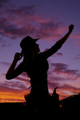silhouette of a cowgirl on a saddle hand up and out