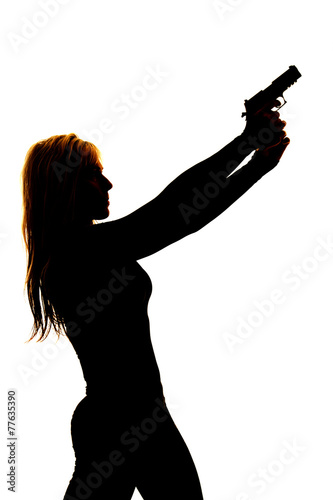 Leinwanddruck Bild silhouette of a woman pointing a gun to the side close