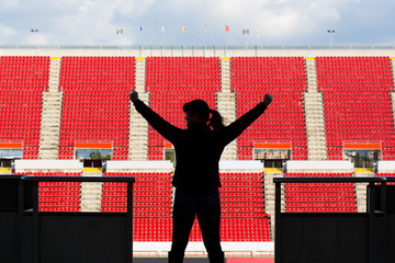 female football fan from behind in a empty stadium