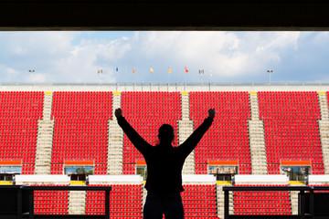 silhouette of female football fan in a empty stadium