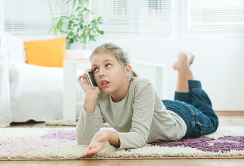 Girl lying in the living room and using the telephone