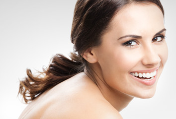 Cheerful smiling brunette woman, against grey