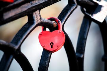Красный замок в форме сердца на ограде