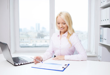 smiling businesswoman reading papers in office