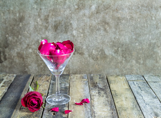 Fresh red rose in glass on wooden background