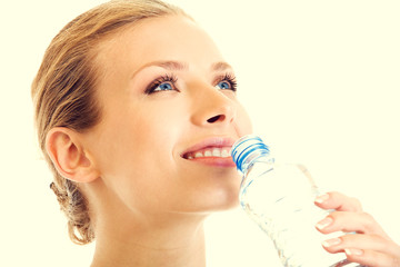 Portrait of beautiful young blond woman drinking water