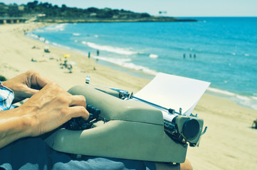 young man typewriting on the beach