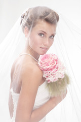 Beautiful smiling bride in the veil with bouquet