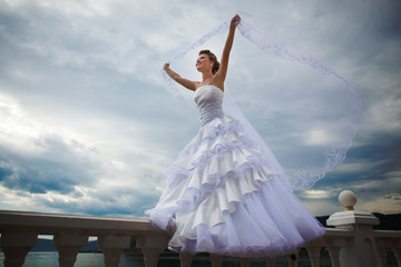 Beautiful Bride walking on the terrace with veil