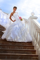 Beautiful bride standing on stairs in the sunny day
