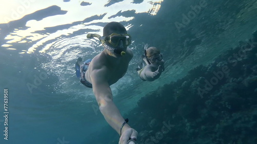 Fotobehang Koraalriffen man with his son dives and makes selfe under water