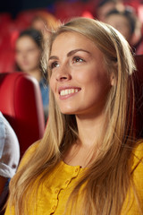 happy young woman watching movie in theater