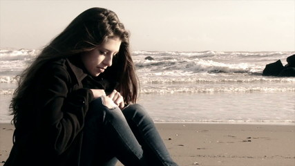 Girl on the beach sitting depressed in the winter