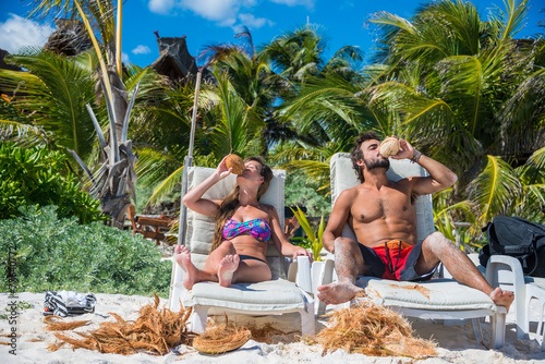 Cute Couple drinking Coconut at Tulum caribbean beach. Riviera M - 77640772