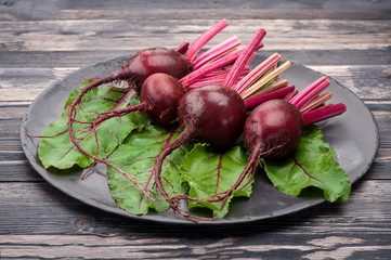 Raw beets with leaves on a dark background