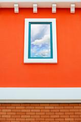 Sky reflection in window glass on orange wall