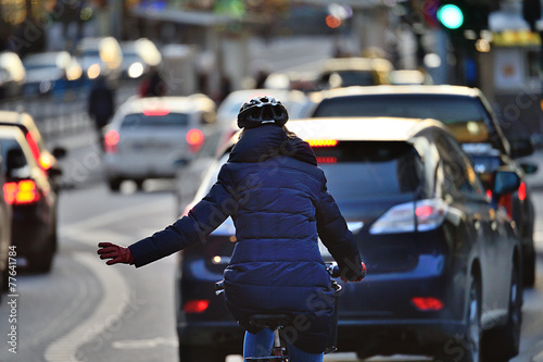 Leinwandbild Motiv Winter city scene. Woman on bike in traffic