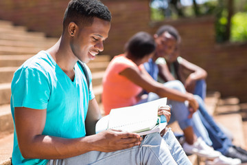 african american university student reading a book