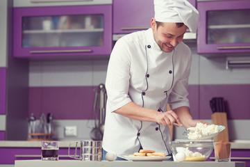 Tiramisu cooking concept. Smiling man in cook uniform