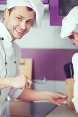 Portrait of a smiling male chef with his coworker cooking food