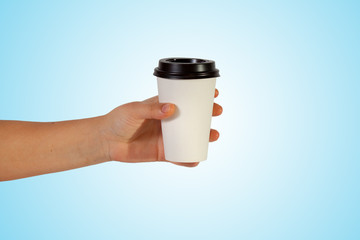 disposable cup of coffee in hand on blue background