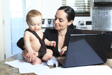 busy mother with her baby in the kitchen table
